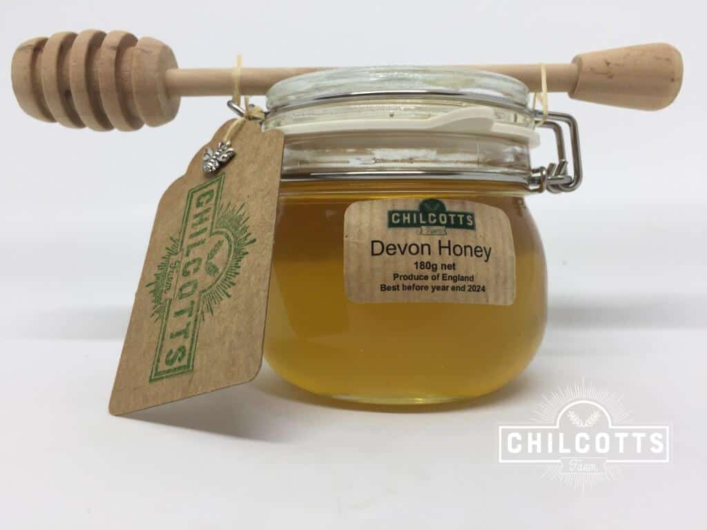 Pure clear honey in jar with honey dipper